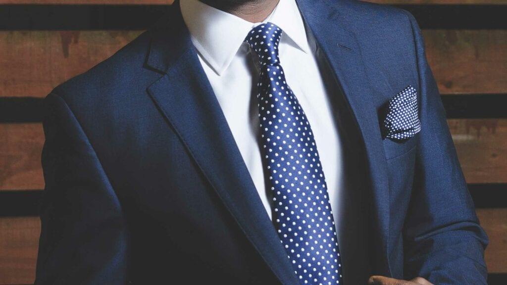 Blauer Männeranzug mit getüpfelter Krawatte und Einstecktuch.