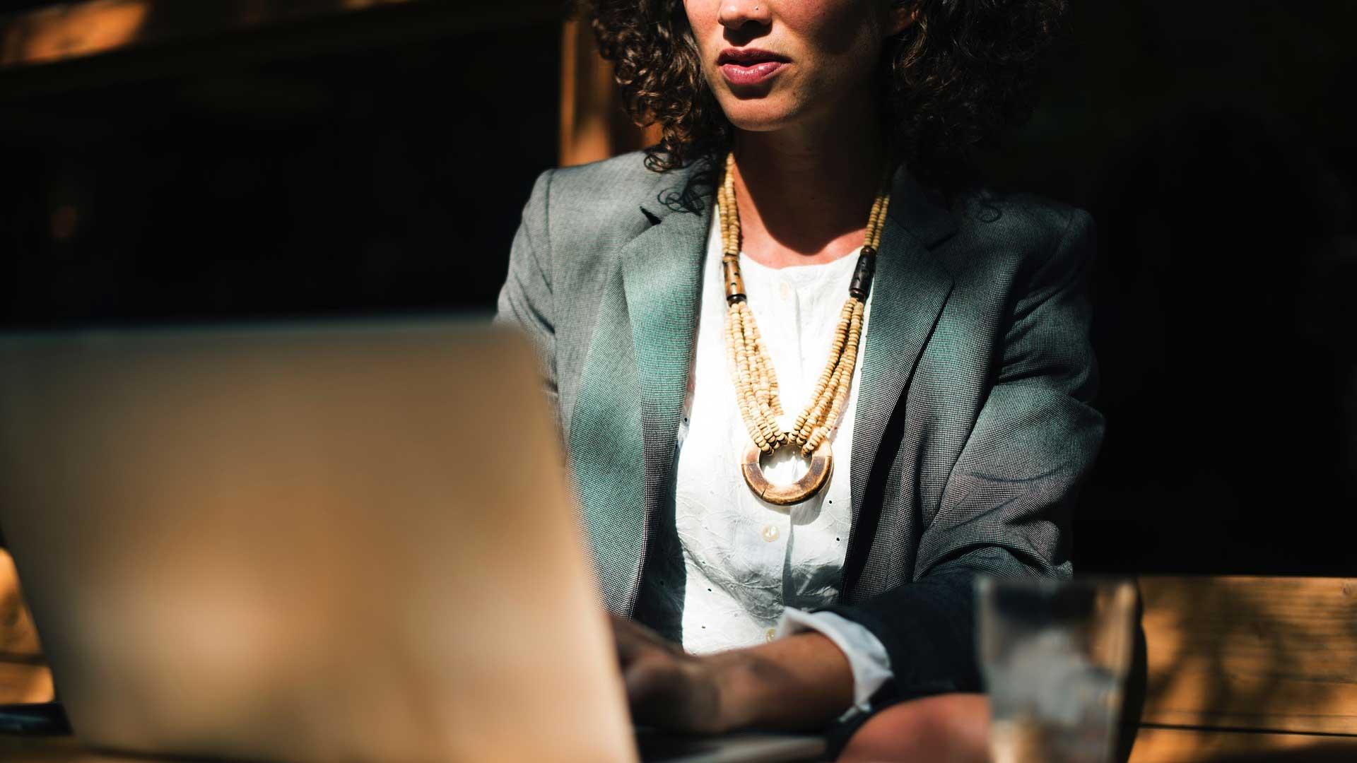 Frau mit Anzugskostüm arbeitet am Laptop.