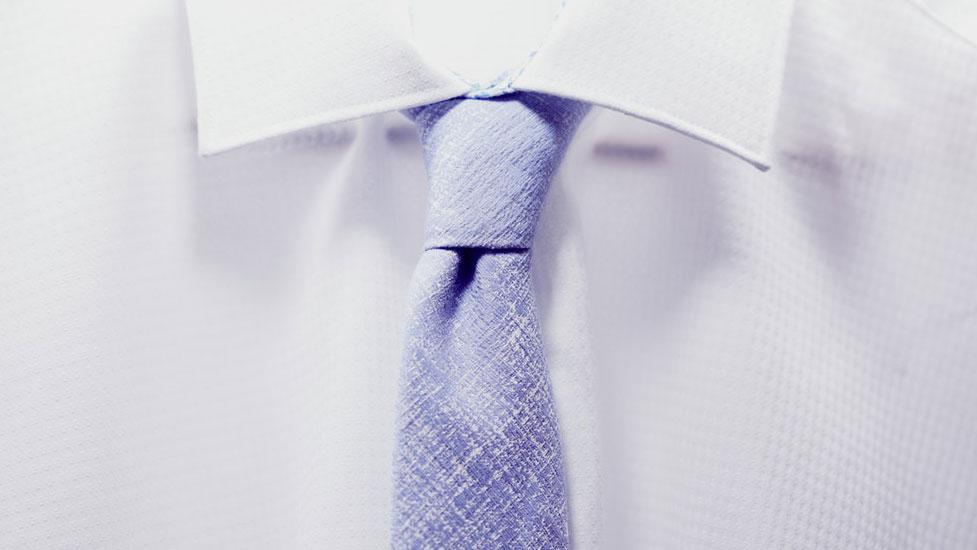 Weisses Hemd mit hellblauer Krawatte mit Struktur.