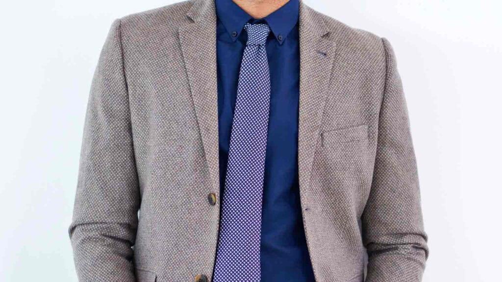 Graues Sako mit dunkelblauem Hemd und blau-weisser Krawatte.