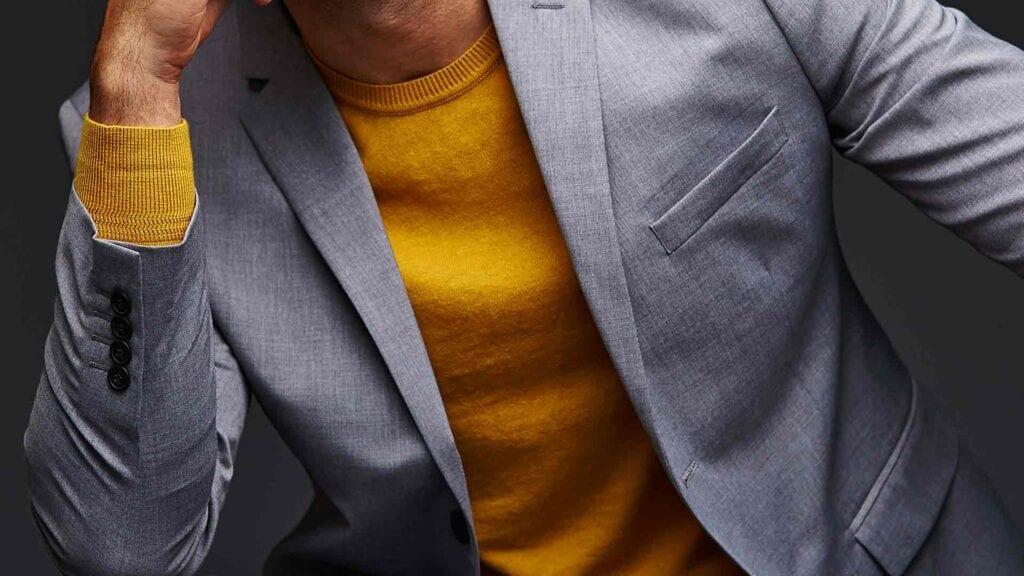Graues Casual-Sako mit senf-gelbem Pullover darunter.