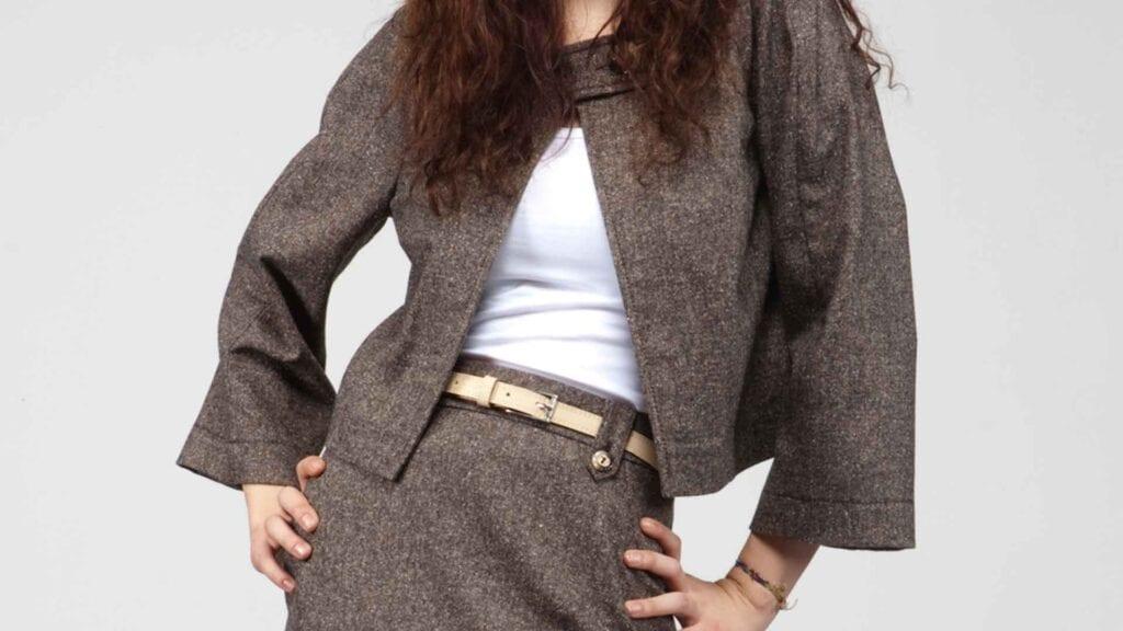Braun-graues Damenkostüm mit weisser Bluse und beigem Gurt.