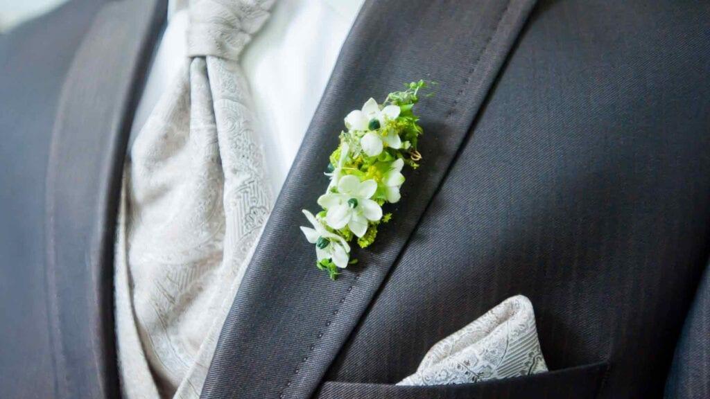 Dunkles Hochzeits-Sako und helle Krawatte mit Muster sowie eine Ansteck-Blume.
