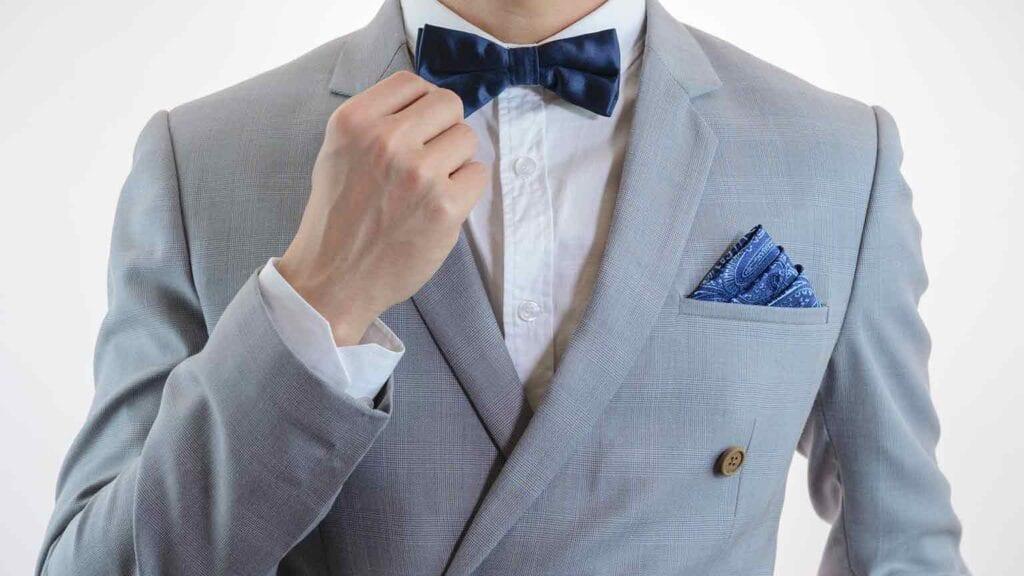 Grauer Business-Anzug mit weissem Hemd und blauer Fliege & Einstecktuch.