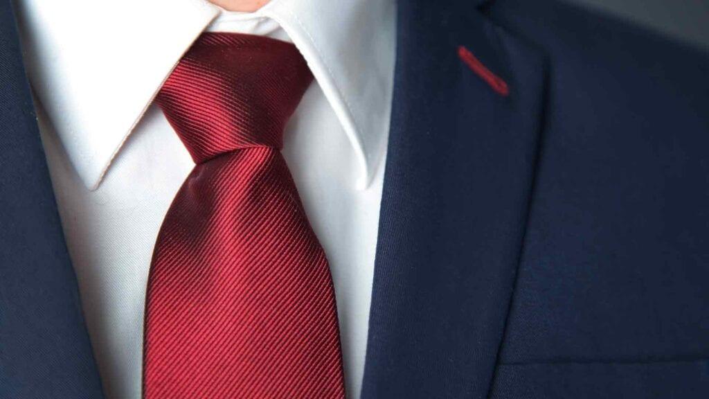 Blauer Business-Anzug mit weissem Hemd und roter Krawatte.
