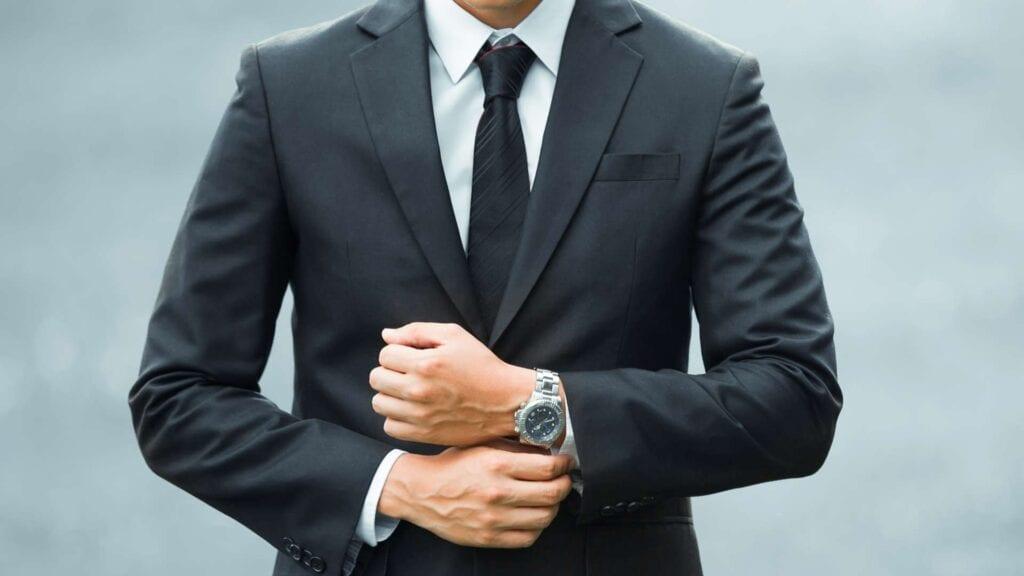 Schwarzer Business-Anzug mit weissem Hemd und schwarzer Krawatte.