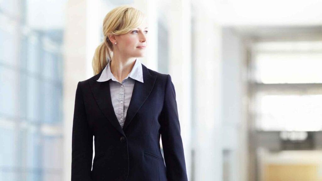 Blonde Dame im dunklen Anzugskostüm mit hellblauer Bluse.