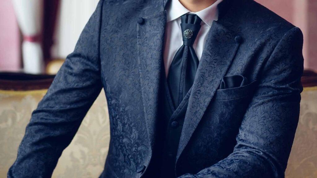 Dunkler Hochzeitsanzug mit Muster und dunkler Krawatte und weissem Hemd.