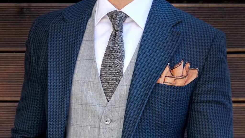 Blau-karrierter Casual Sako mit grauer Weste und gestrickter Krawatte.