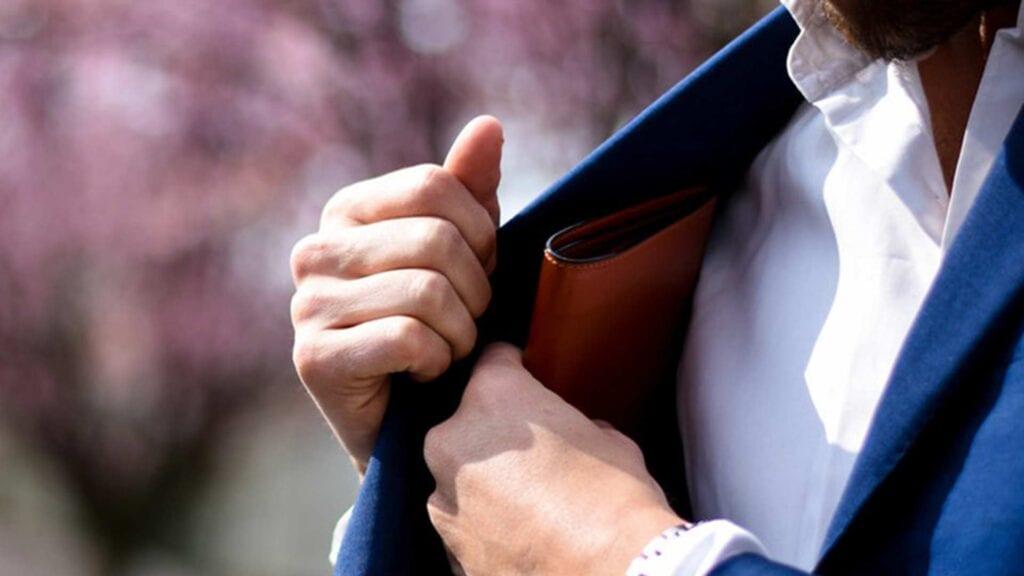 Mann mit Anzug holt sich Brieftasche aus der Sako-Tasche.