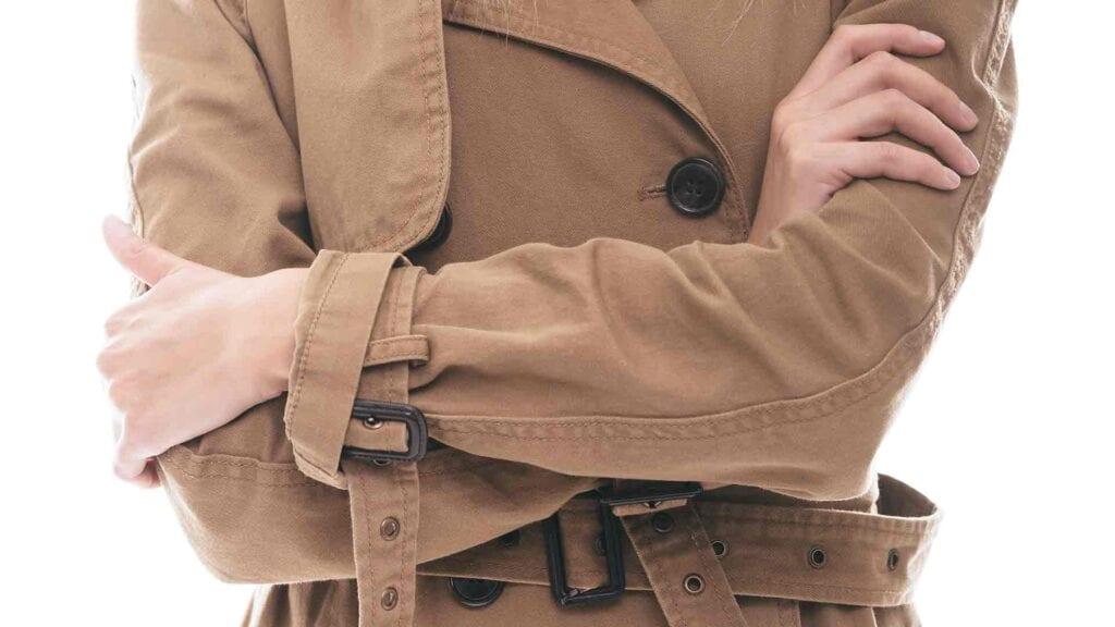 Frau mit beigem Mantel verschränkt ihre Arme.