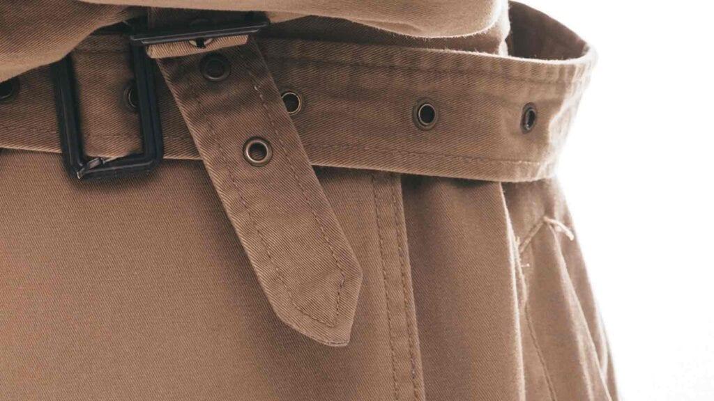 Beiger Mantel mit Gürtelschnalle.