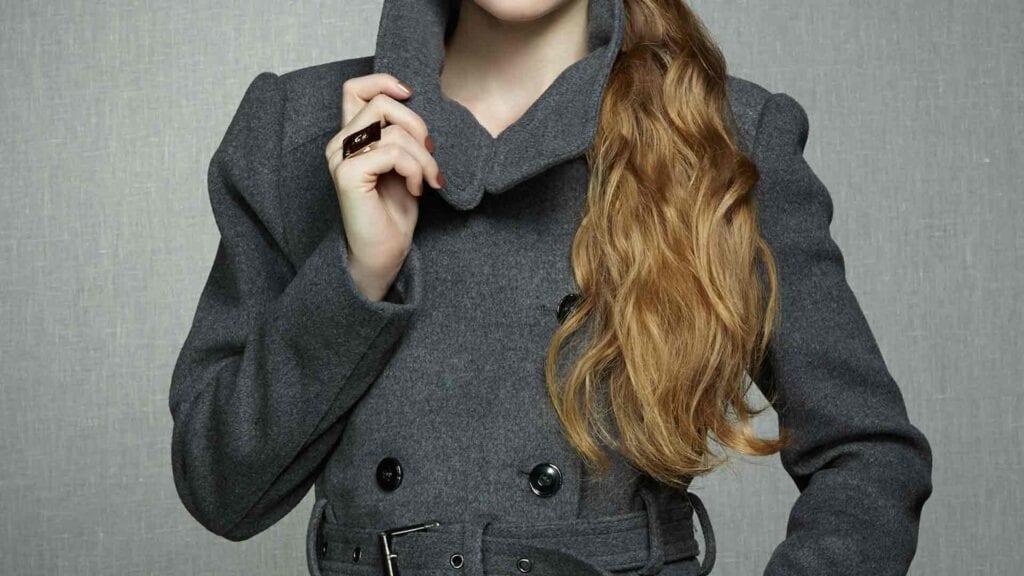 Frau trägt grauen Wollmantel.