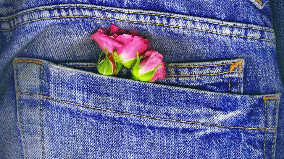 Jeans-Tasche mit pinken Rosen darin.