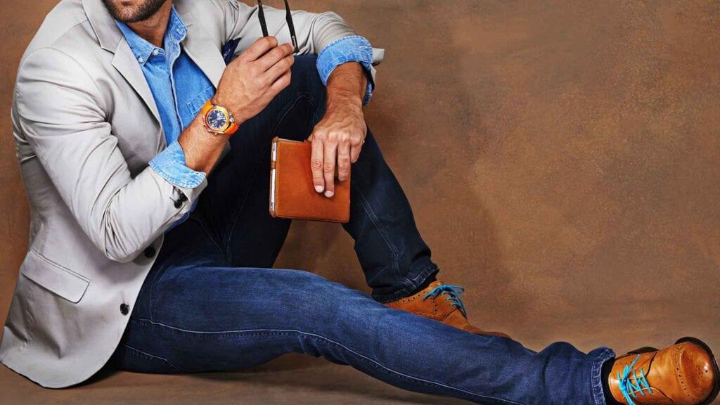 Mann sitzend mit hellem Casual-Sako und Jeans-Hose.
