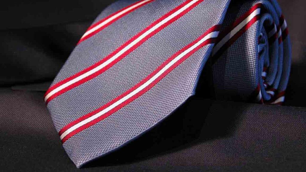 Grau-blaue Krawatte mit rot-weissen Linien.