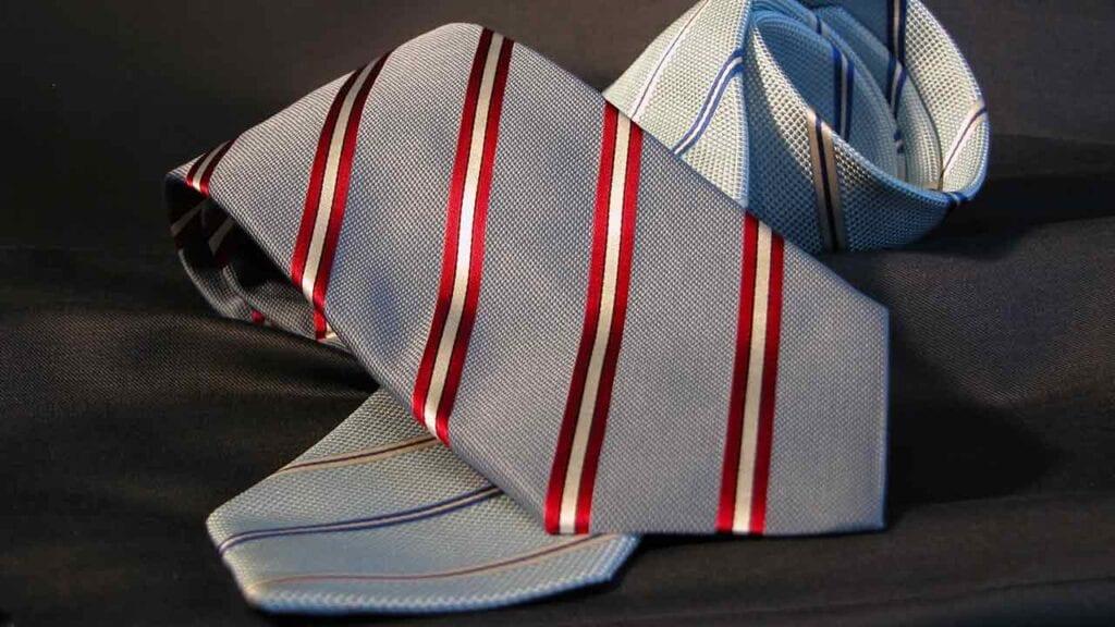 Zwei hell graue Krawatten. Die eine mit rot-weissen Linien, die andere mit blau-beigen Linien.