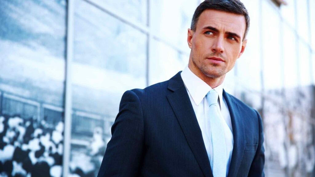 Mann im Business-Anzug mit weissem Hemd und hellblauer Krawatte.