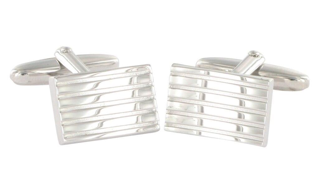 Rechteckige, silberne Manschettenknöpfe mit linienförmigen Einwölbungen.