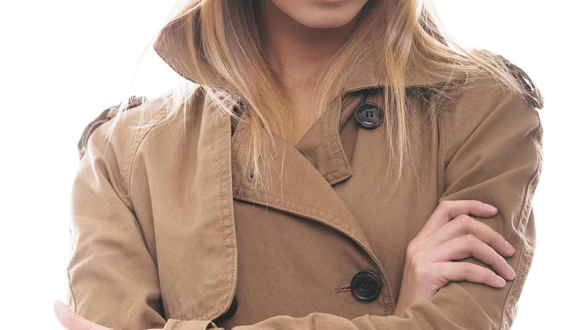 Blonde Frau trägt einen beigen Mantel.