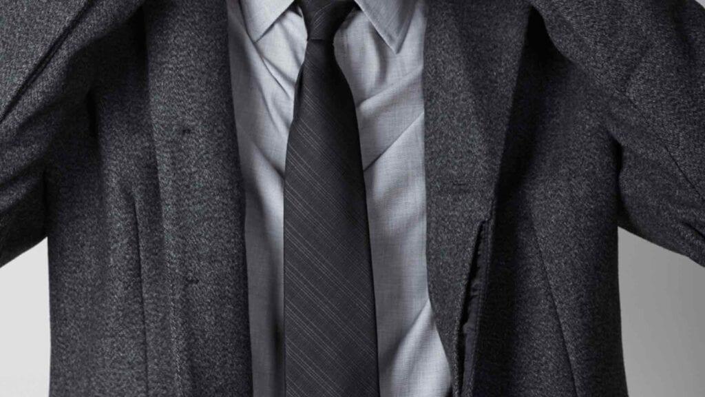 Grauer Herrenmantel mit dunkler Krawatte und hellgrauem Hemd.