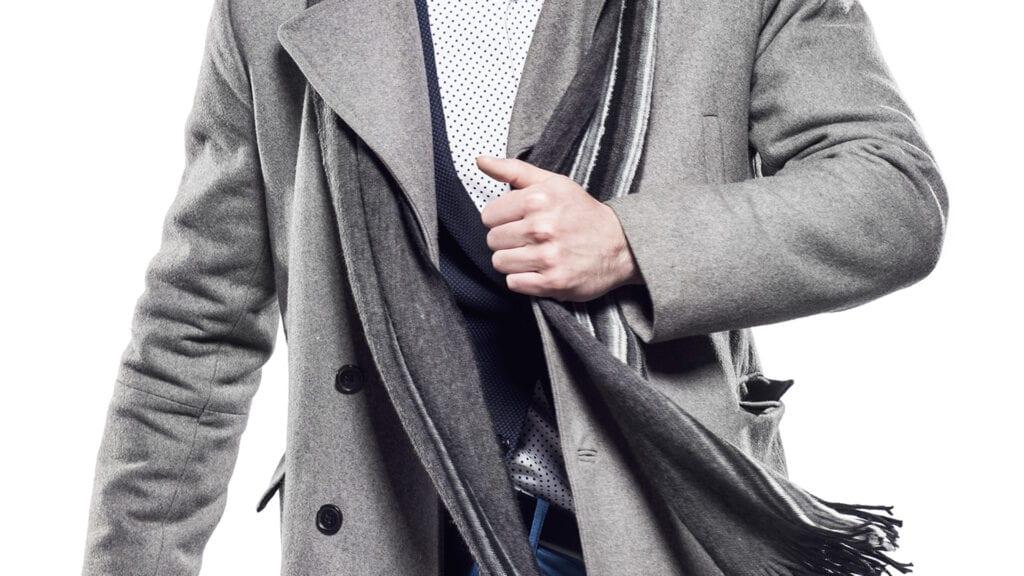 Grauer Herrenmantel mit grauem Schal und weissem, getupftem Hemd.