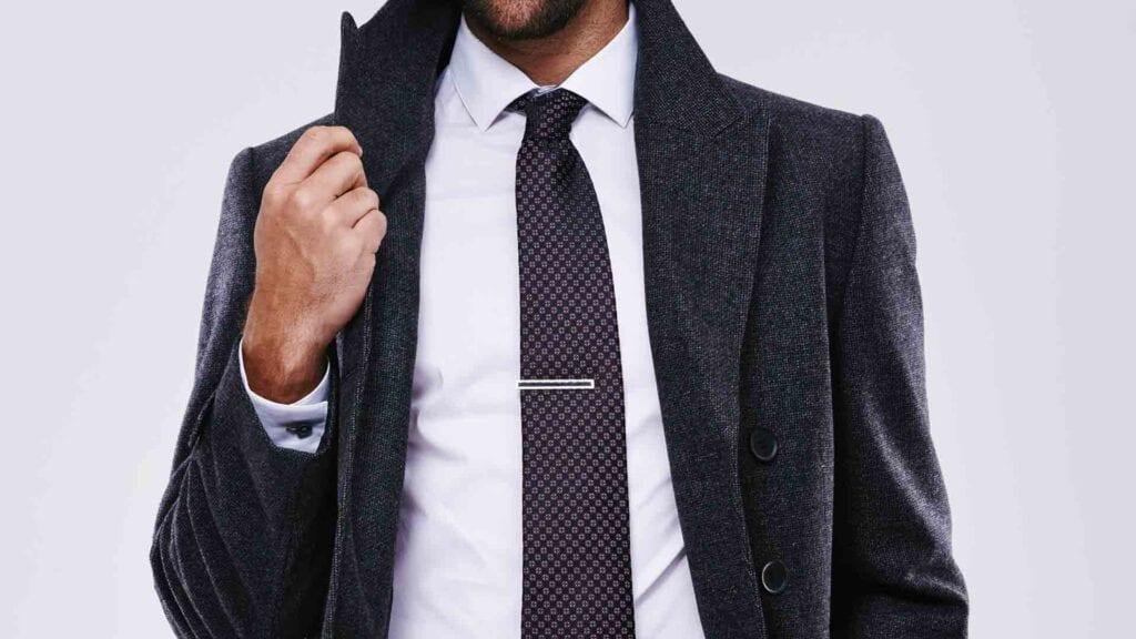 Schwarzer Herren-Mantel mit weissem Hemd und Krawatte.
