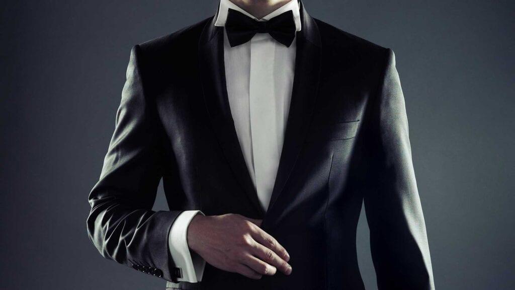 Dunkler Smoking mit weissem Hemd und schwarzer Fliege.