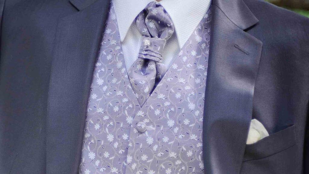 Grauer Hochzeitsanzug mit geblümter, lila-farbener Weste.
